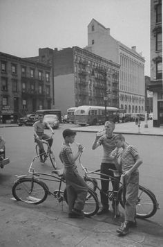 Young boys riding bicycles and drinking sodas. Photograph by Cornell Capa. New York City, July 1948.