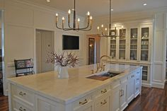 chandeliers over island, marble, brass pulls, white, built-in china cabinet