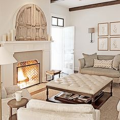 neutral colors, simple botanicals, beautiful fireplace, tufted ottoman with shelf beneath