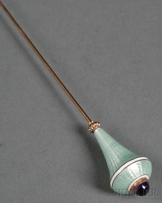 Enamel and Amethyst-mounted Hat Pin, Europe or Russia, late 19th century, long goldwashed stem with tapered ovoid finial with pale green basse taille enamel, ending in a sugarloaf amethyst finial.