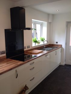 Autograph Cream Gloss - A simple yet effective design in creating a sophisticated and contemporary look in this kitchen! The light walnut worktop and smart black CDA cooking appliances are the perfect match. Even the cat is a fan...