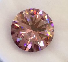 5.50Carats, Pink Moissanite. VVS1 Excellent Cut.Pink/deep pink depending on the light. Brilliant Round Cut. Near Flawless. This stone is full of Fire and at 5.50Carats!!! The price is right. But, I do accept payments. Want to see it in action? BIG and Beautiful!!! Pink Glam. Authentic test positive for diamond and Moissanite.