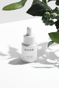 Nuori all white packaging with dropper. White shooting flatlay surface with leaves and foliage