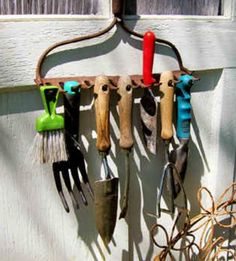 An old metal rake head makes a great garden tool holder on the side of a potting shed