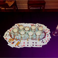 Simple James Bond themed party centerpiece. Just need two decks of cards, some votive candles and dice.