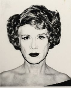 A photograph of Andy Warhol dressed in drag. He wears very pale face makeup, a bold lip, and a short, curly wig.