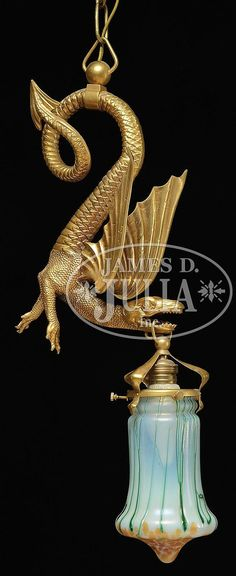 """Loetz hanging lamp has cast bronze dragon with wings and scaled tail. Dragon is finished in a bright gold patina and fixture supports a Loetz shade with orange iridescent oil spot decoration around the bottom and green iridescent applied threading descending from the fitter against an opalescent background. Fixture and shade are unsigned. SIZE: 25"""" from top of fixture to bottom of shade not including chain. CONDITION: Very good to excellent. There is no ceiling cap. 9582-4"""