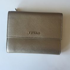 FURLA Wallet (Bronze/Gold) Beautiful pre-loved FURLA gold wallet. It fits many credit cards, has two slots for bills. Also a separate zippered area for coins. It has a small indentation seen in picture 3, but overall in great condition. Easily fits in smaller purses, like cross body's or clutches. It's adorable! Furla Bags Wallets