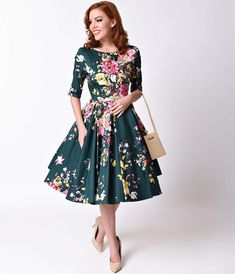 Made for a fabulous frolic! The Vintage Hepburn dress has arrived fresh from The Pretty Dress Company in a gorgeous hunter green and signature floral Seville print, cast in a classic retro dress design! Darling details include a chic high boat neckline which flows into a flattering back 'V', with half length sleeves that finish above the elbow. A thick cinched waist and full box pleated circle swing skirt creates ethereal movement, crafted in stretch cotton and fully lined. You'll be the ...