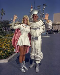 """'Guests visiting Tomorrowland in the 1950s and 1960s would encounter a unique original Disneyland character that symbolized Americans' interest in space exploration. In this rare photo from the summer of 1960, the Tomorrowland """"Spaceman"""" is apparently joined by """"Spacewoman.""""'"""