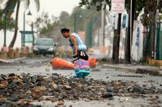 A woman pulls a travel case on a rock scattered road in the aftermath of Hurricane Irma in Fajardo, Puerto Rico, on Sept. 7, 2017. (Photo: Ricardo Arduengo/AFP/Getty Images)