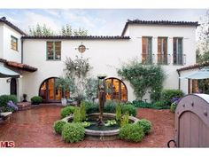 Tuscan. I would add pretty flower boxes under all the windows. And around fountain