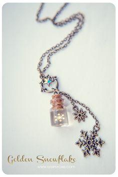 Un collar de botella de cristal pequeña hecha a mano con copo de nieve de Metal dorado pequeño dentro de. :)  La botella se llena con resina epoxi con