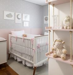 This is such a beautiful baby girls nursery with such a cute wall with prints above the crib. The hanging shelf with the decor on it is too cute!