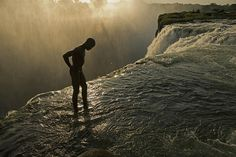 The 355-foot (108 meter) drop of Victoria Falls just inches away, a swimmer stands at the lip of a hidden pool—an eight-foot-deep (2 meter) divot in the riverbed rock—accessible only when the Zambezi River runs low (aka Devil's Pool). By Annie Belt.
