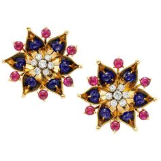 Cartier, A Pair of Ruby, Sapphire and Diamond Ear Clips, each designed as a flower head, set with 6 cabochon sapphires weighing approximately 4.50 carats and 6 cabochon rubies weighing approximately 4.00 carats, the center highlighted by brilliant-cut diamonds weighing approximately 1.00 carat, H-I Color, VS Clarity, mounted in 18K yellow gold, signed Cartier, circa 1940.