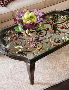Everett Floral & Scroll Coffee Table - Jewel: Hammered scrolls and jeweled flowers create an expansive, sparkling garden beneath a beveled glass top on our Everett Floral & Scroll Coffee Table. Brass-patinaed steel table with hammered finish from Vietnam; dimensional metal flowers and butterflies forged in Rhode Island, finished in 14K gold. Artisans in upstate New York hand-paint layers of enamel and hand-set more than 3500 crystals.