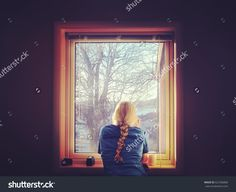 Blond woman looking out the window. View from a dark room.