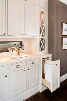Kitchen with mink brown paint color, creamy white shaker cabinets, marble countertops, mirrored backsplash and built-in towel rack drawer.