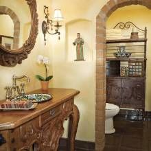 This full bath was converted to a spacious powder room. Mexican in spirit, the carved wood vanity contains a colorful Talavera sink. Following a motif seen elsewhere in the home, an arched-brick surround defines the separate commode area. An old baker's rack provides storage and  display space.