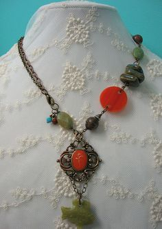 I suppose orange, green and turquoise blue might be considered an interesting color combination but I love the way it works in this vintage assemblage necklace. A carved green stone fish hangs from a vintage orange enamel pendant. The pendant is brass-plated copper and the plating has started to wear off giving it a warm duo-tone finish. One side of the necklace includes a whimsical variety of beads including blue ceramic triangles, vintage orange moonstone plastic, leopard jasper…