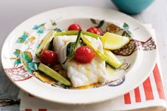Baked fish with tomato, zucchini and potato wedges