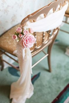 Romantic chair decor with beautiful draping, pink roses, and strands of pearls.