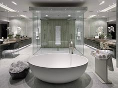 Striking modern design bathroom centers acres of marble flooring and a pair of oversize natural wood vanities around an immense glass cube shower at center. Oval pedestal tub stands in foreground, while full wall size mirrors amplify visual space.