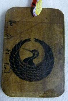木札で作っている北海道かるたに、鶴丸家紋を付け、柿渋で染め、一閑張りをして作りました。 紐は正絹の柄入りの縮緬の生地でループを作り、中には毛糸を入れています。...|ハンドメイド、手作り、手仕事品の通販・販売・購入ならCreema。