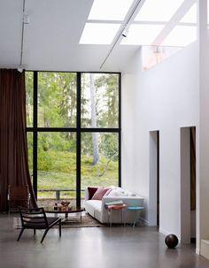 Black window frames, light well, and concrete floor