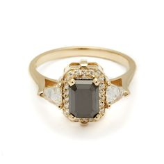 The Bea Halo is a three stone ring featuring a stunning emerald cut black diamond, encircled with a white diamond pavé halo and accompanied by inverted set diamond trillions.