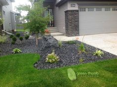 Rundle rock beds with snap edging and an accent boulder. The black Rundle ties in with the colours on the house and brings out the colours in the plants. The snap edging provides an invisible edge.