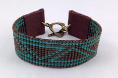 Beautiful loom woven beaded cuff made with 11/0 metallic bronze and turquoise glass seed beads, genuine leather tabs fastened with a brass toggle