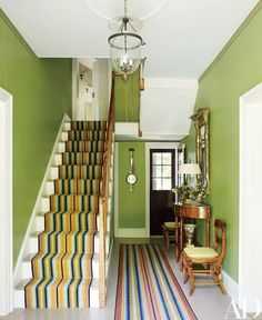 Striped runners by Woodard & Greenstein animate the entrance hall, which is lit with an antique lantern; the early-19th-century tiger-maple demilune table and chairs were chosen because they match the banister, and the gilt-wood mirror is antique American.