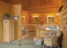 Handcrafted Chink Style Log Master Bathroom with soaking tub. This open design makes the bathroom feel much larger than it is. #Cariboucreekloghomes #loghomeinteriordesign