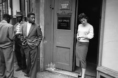 21 July 1956: Andria Loran, a model who was democratically elected Queen of Soho 1956, stands in the doorway of the Mambo Club, keenly noticed by an onlooker.(Hulton Archive/Getty Images)