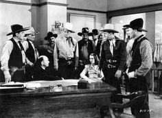 a non-bobbed Louise Brooks & a non-bobbed John Wayne hold court in 1938's Overland Stage Raiders
