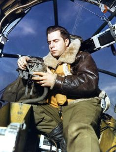 While still the ground at an unspecified base, American Captain Louis Detoni adjusts his oxygen mask as he sits in front of what appears to the bombardier's position in the nose of heavy bomber, England, 1940s. (Photo by PhotoQuest/Getty Images)