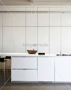 White kitchen with floor-to-ceiling fitted cupboards & recessed ceiling lamps – living4media