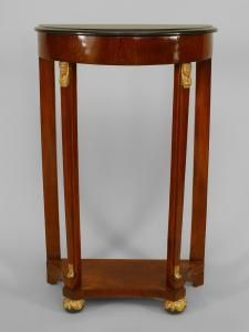 Austrian Biedermeier (circa 1830) narrow mahogany demi lune console table with gilt Egyptian heads and a platform stretcher base above ball feet with a black marble top.