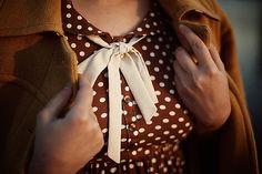 brown polka-dot dress with white silk necktie.