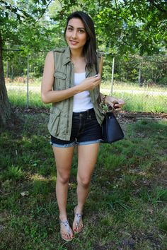 Shop this look for $74:  http://lookastic.com/women/looks/vest-and-tank-and-shorts-and-satchel-bag-and-thong-sandals/2464  — Dark Green Vest  — White Tank  — Navy Denim Shorts  — Navy Leather Satchel Bag  — Grey Print Leather Thong Sandals