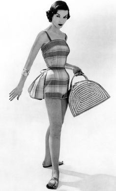 Model and designer both unknown. This beachwear is a romper cinched at the waist to emphasize a woman's small waist and promote her figure. Dated 1955.