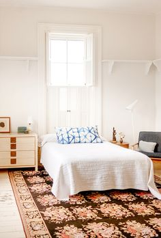 White bedroom with blue tie-dyed pillow and light wood side table/dresser