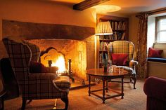 Lovely English style interior by the cozy fire, with plaid chairs.