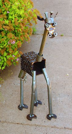 This Scrap Metal Giraffe is on spindly legs, and will keep your low bushes nicely pruned. :)