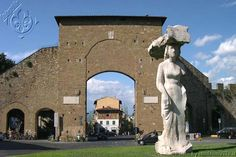 Large Pistoletto statue depicting a woman departing the city gates carrying an enormous bundle on her head. Florence's austere city gate was once the site of the Fiera dei Contratti—the Contracts Fair—at which fathers sold their daughters into a contracted marriage, often forcing them to dance provocatively in an effort to secure higher dowries.