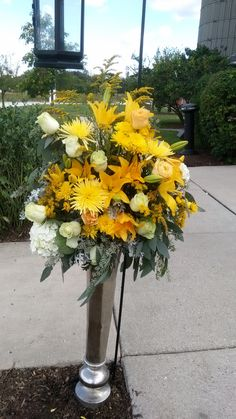 """Wedding entrance floral pieces in silver urns with black lanterns. Made with white hydranges and roses, mixed yellow roses, spider mums, lilies, seeded eucalyptus, and dusty miller. Designed and created by """"WOW"""" Event Design and Coordination. #yellowweddings #greyweddings #wedding flowers #entrance flowers #lanterncenterpieces #dustymiller #rusticwedding"""