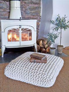 Cojín tejido de lana gruesa blanco frente a una chimenea