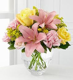 FTD® proudly presents the Sweet Effects™ Bouquet by Vera Wang. An expression of grace, set to fascinate, this bouquet of pink Asiatic Lilies, pink double lisianthus, yellow roses, solidago and fresh, lush greens are perfectly arranged in a clear modern glass vase, to create a lovely way to bring sophisticated beauty into their day.